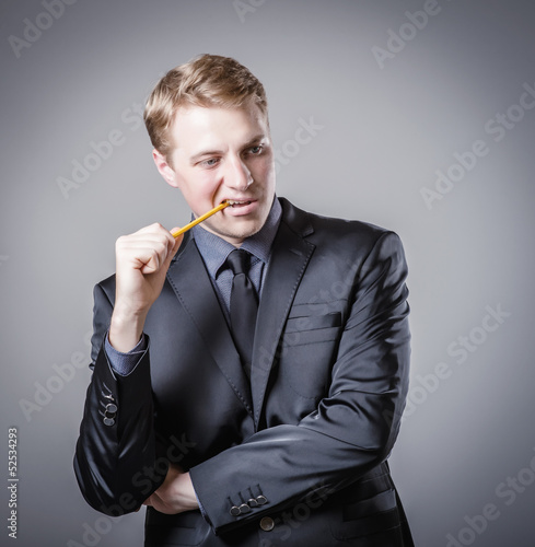 Young man biting a pencil