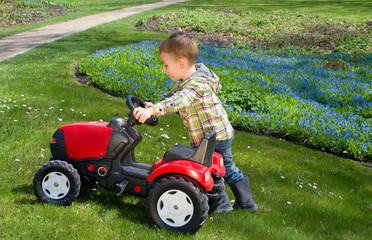 Klienkind schiebt Traktor