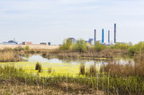 Industrial suburbs with smokestacks near large water ecosystem. poster