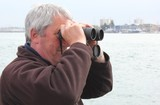 A white male using binoculars along the coast
