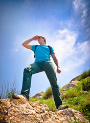 young healthy man hiking in the mountains looks into the distanc