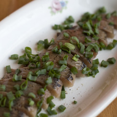 Herring fillet with green onion on a plate