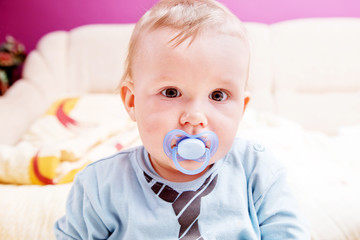 Young baby boy with a dummy in his mouth portrait