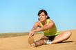 Athlete woman stretching leg on beach