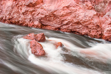 Flowing water around red rocks