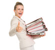 Business woman holding stack of folders and showing thumbs up