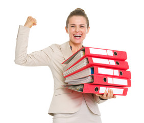 Business woman holding stack of folders and showing biceps