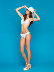 model posing in white bikini with hat