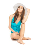 model sitting in swimsuit with hat