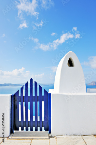 Traditional greek gate and chimney overlooking the caldera in Oi