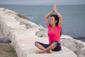 Schöne Frau bei Yogaübung am Meer