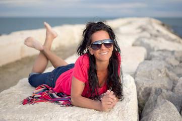 Schöne lächelnde Frau am Meer mit Sonnenbrille