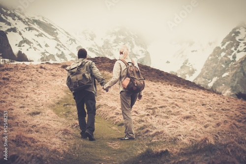 Couple of hikers with backpacks walking in the mountains