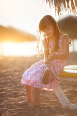 little girl sitting on the beach at sunset