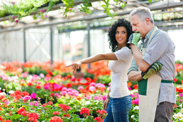 Female customer choosing flowers in a greenhouse