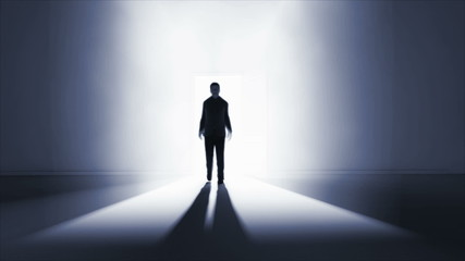 Man walking in a dark room with light coming from behind