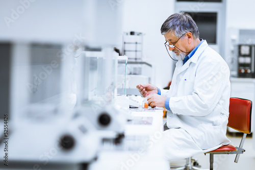 Senior male researcher carrying out scientific research in a lab - 52554426