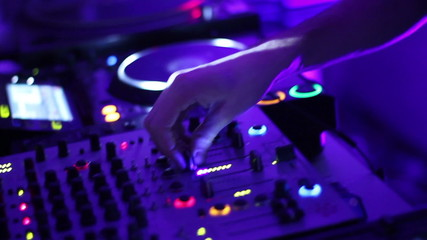 DJ hands tweak controls on turntable record deck in night club.