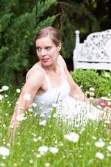 Schöne Frau im Frühling auf einer Wiese sitzend