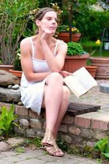 Junge Frau mit Buch im Garten sitzend