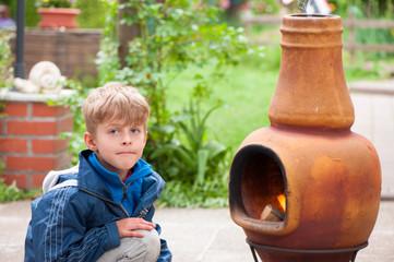 Kleiner Junge sitzt vor einem Ofen und wärmt sich