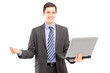 Young man in a suit holding a laptop and gesturing with hand