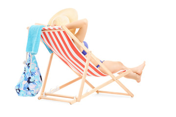 Young female in bikini lying on a beach chair