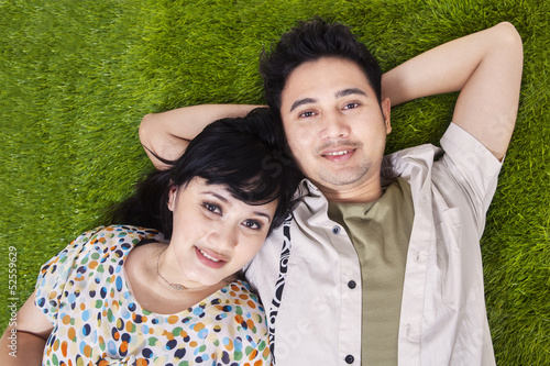 Asian couple laying on green grass