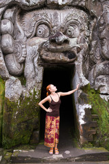 Young woman standing in the demon mouth at Goa Gajah
