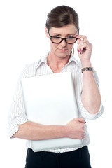 Woman looks over her glasses holding laptop