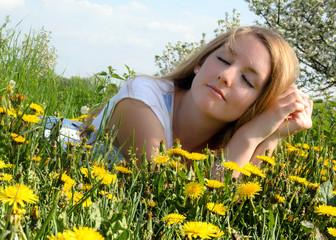 Young woman enjoying the spring between dandelions