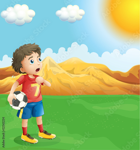 A boy holding a soccer ball sweating