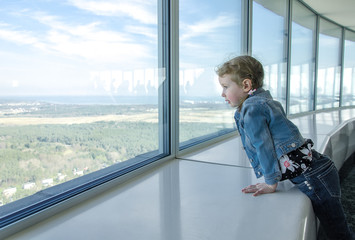 Little girl looking through the window at skyscraper