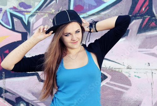 Smiling Teenager Girl Posing against Wall
