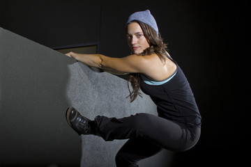 free runner scaling or climbing a wall at night to do parkour