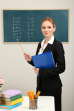 Portrait of teacher woman near chalkboard in classroom