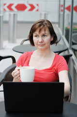 Woman drinking coffee in a outdoor cafe