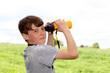 Junge mit Fernglas auf der Wiese