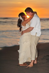 Bride and groom holding hands and kissing barefoot on beach