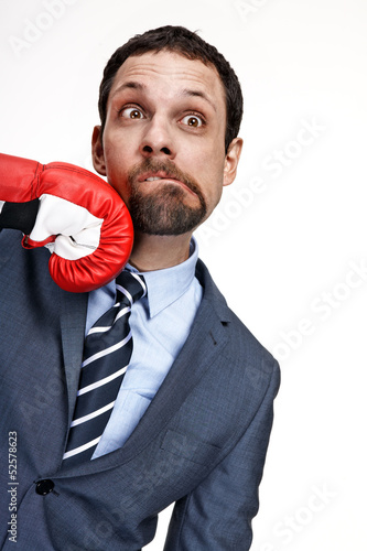 Young business man struck by hand in boxing glove