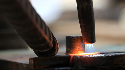 Industrial worker bending steel by using metal torch.
