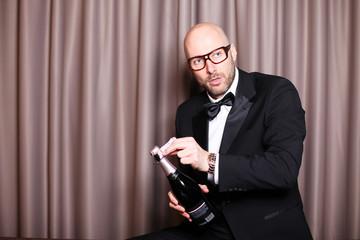 männliches Model posiert mit einer Sektflasche