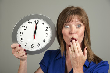 Woman with surprised expression holding a clock