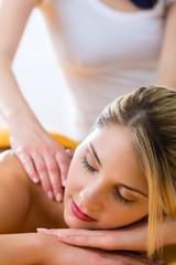 Wellness - Frau erhält Rückenmassage in Spa