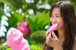 Cute Thai girl is eating pink candyfloss in shade