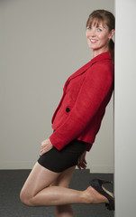 Woman wearing red jacket leaning on a wall