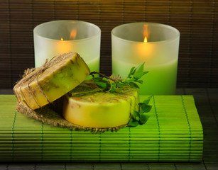 Hand made soap and candles on bamboo mat background