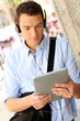 Casual man in town using digital tablet