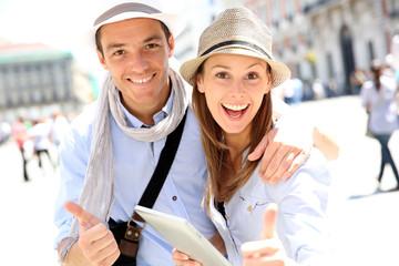 Couple with tablet showing thumbs up