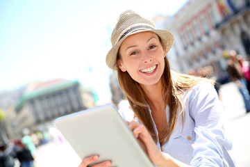 Cheerful girl with hat using tablet in town